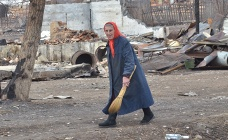 A local resident walking by a burnt out house in the village in Khakassia